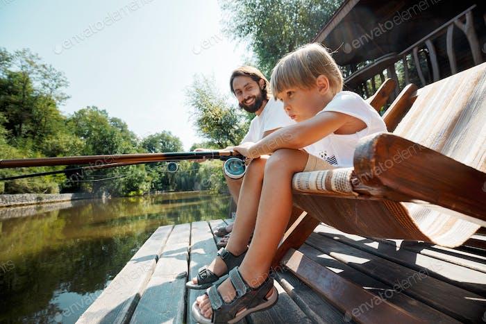 Der kleine blonde Junge und sein hübscher Vater sitzen in Liegen auf dem hölzernen Pier und angeln