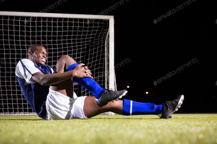Young male soccer player suffering from knee pain on playing field