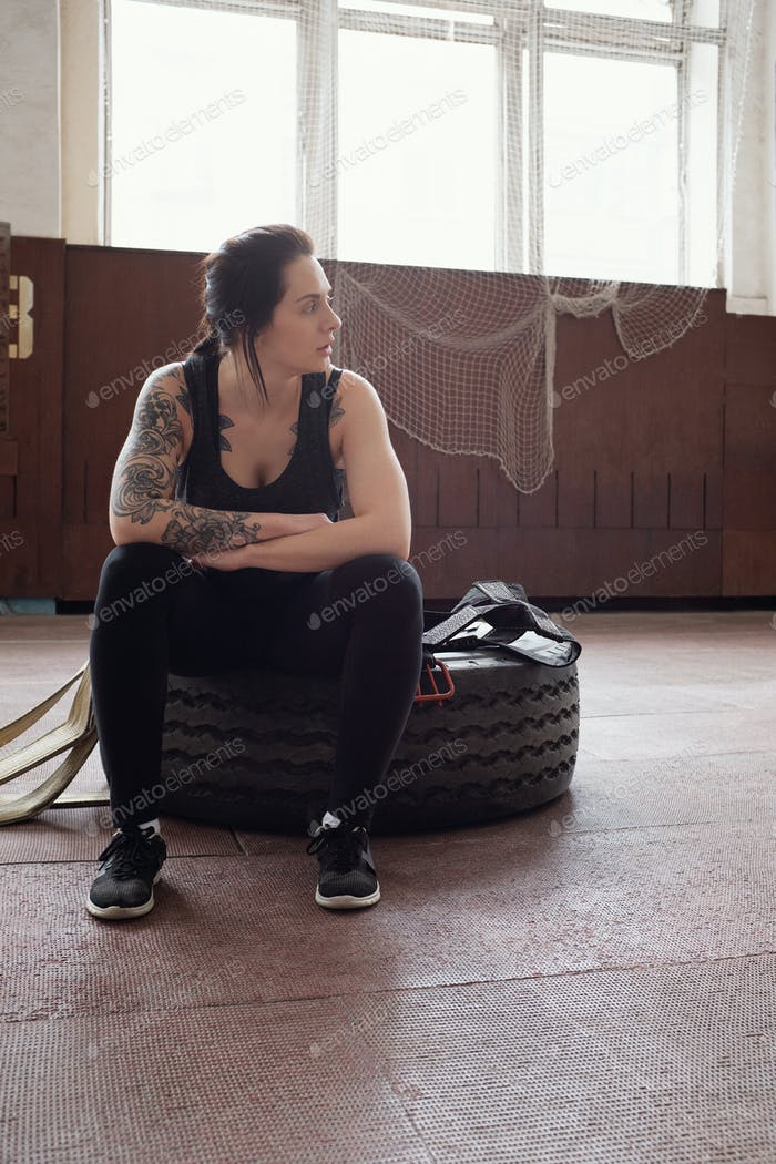 Athletic Caucasian woman with tattooed arms resting on tire after workout