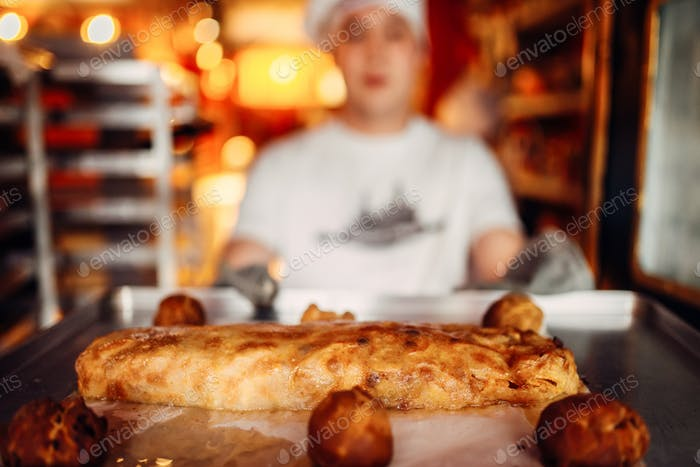 Chef holds baking sheet with fresh cooked strudel