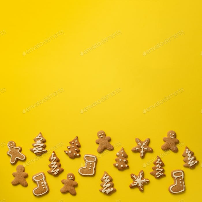 Homemade christmas cookies on yellow background with copy space. Square crop. Pattern of gingerbread