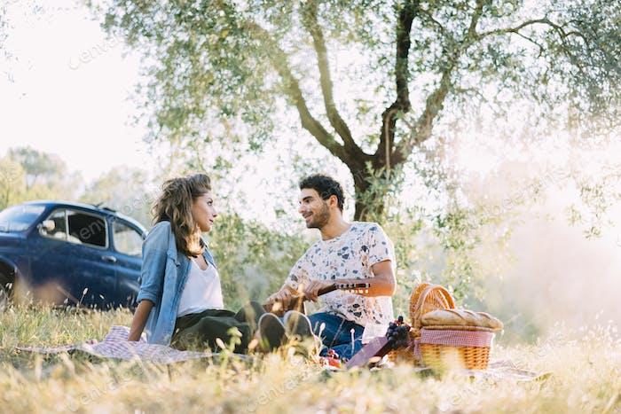 Junger Mann spielt Gitarre während eines Picknicks zu seiner Freundin