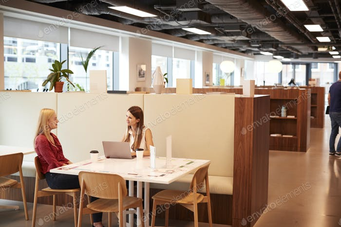 Two Young Businesswomen Having Informal Interview In Cafeteria Area