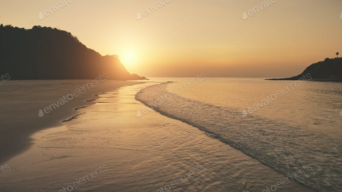 Sunset at ocean waves wash sand beach. Aerial sun set over mountain silhouette. Tropic nobody nature