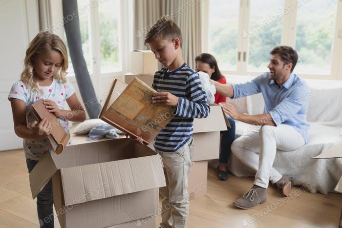 Front view of Caucasian family unpacking cardboard boxes in living room at home