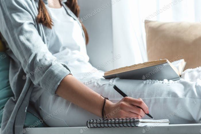 cropped view of girl reading book and writing in copybook