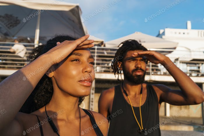 African american man and woman looking in distance outdoors