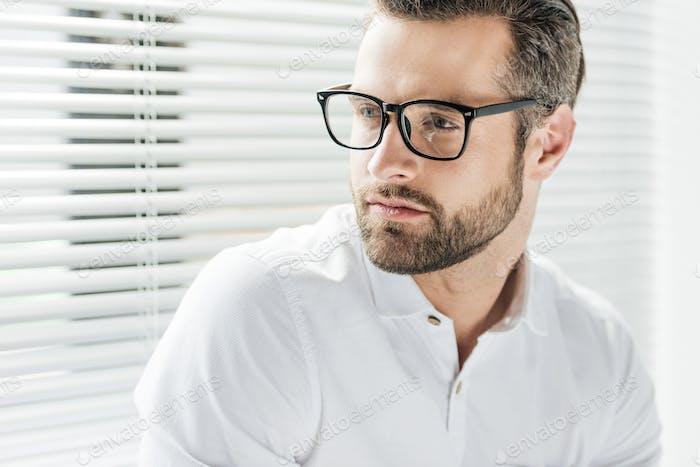 portrait of handsome bearded man in eyeglasses