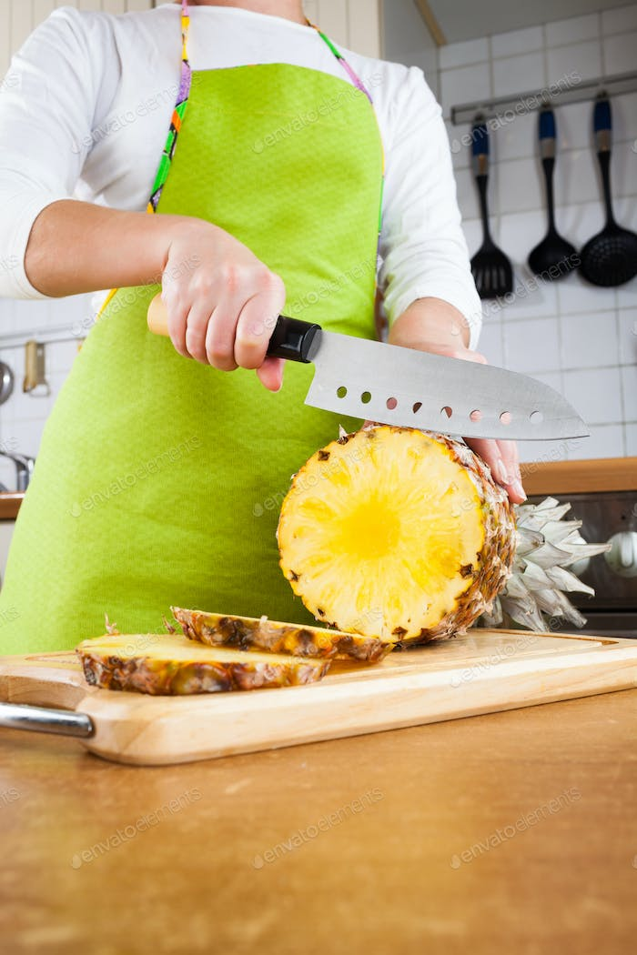 Woman's hands cutting pineapple