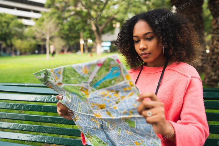 Afro-american woman looking at a map.