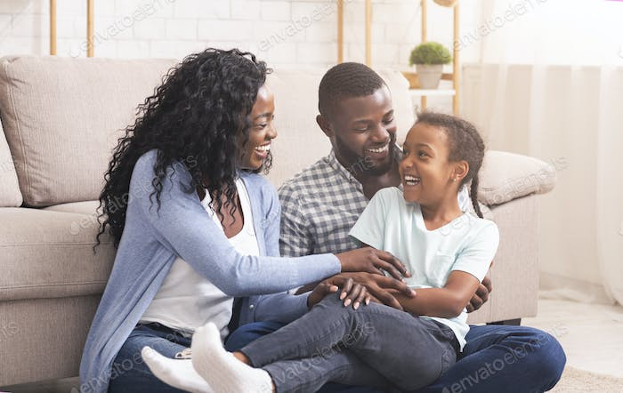 Black parents tickling their daughter and laughing together at home