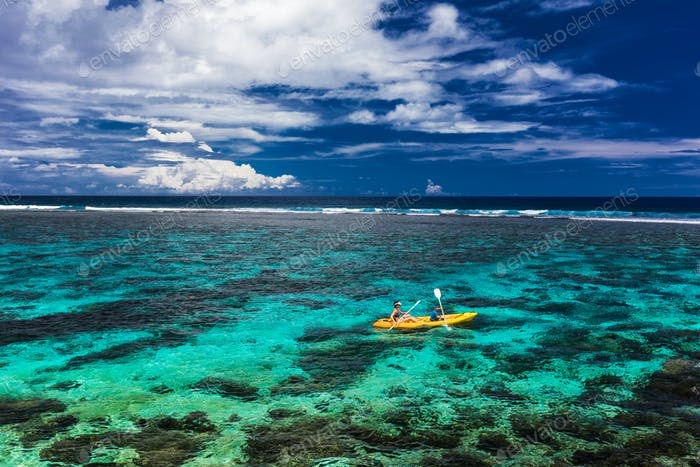 Female and little boy paddling canoe on a lagoon with coral reef