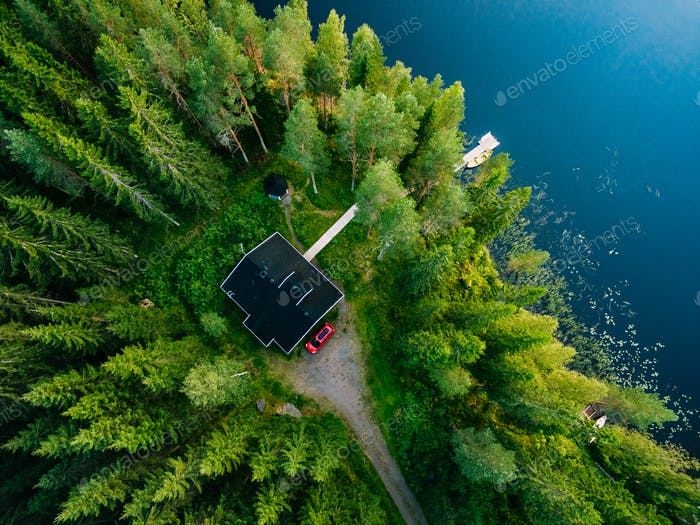 Aerial view of wooden cottage in green forest by the blue lake in rural summer Finland