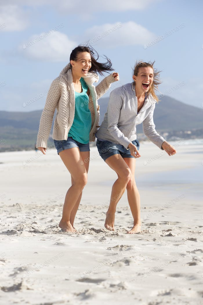 Two barefoot girlfriends laughing on the beach