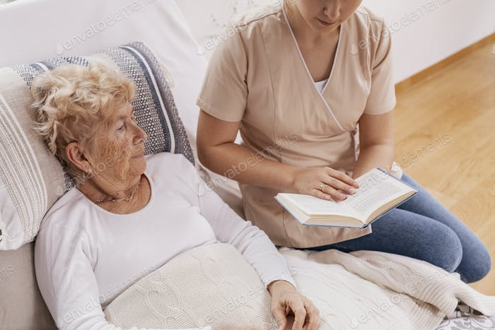 Helpful young carer reads a book to an elderly woman lying in a hospital bed