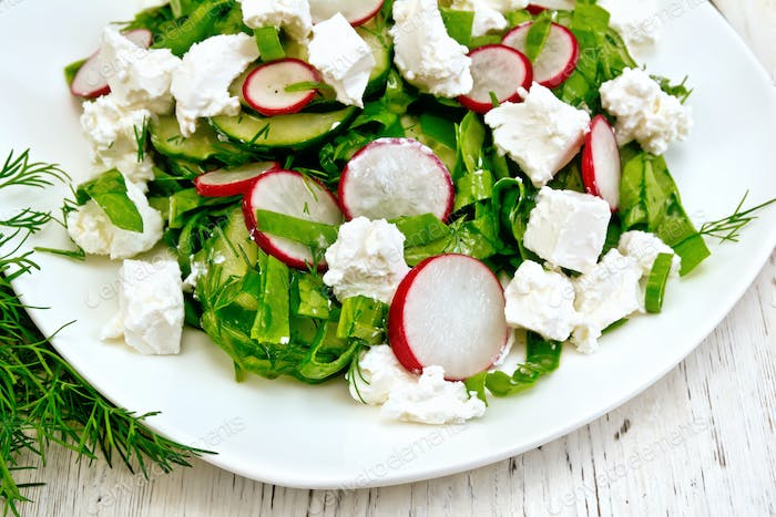 Salad with spinach and cheese in plate on board