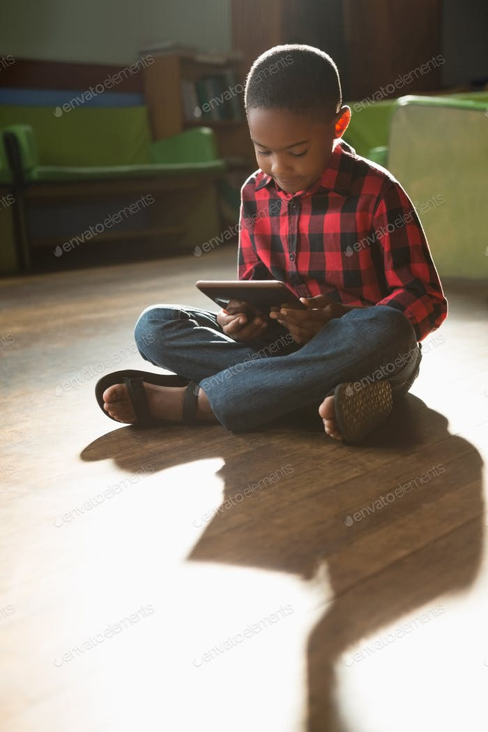 Boy sitting on wooden floor using digital tablet