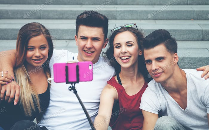 Group of friends with mobile phone on selfie stick and taking picture