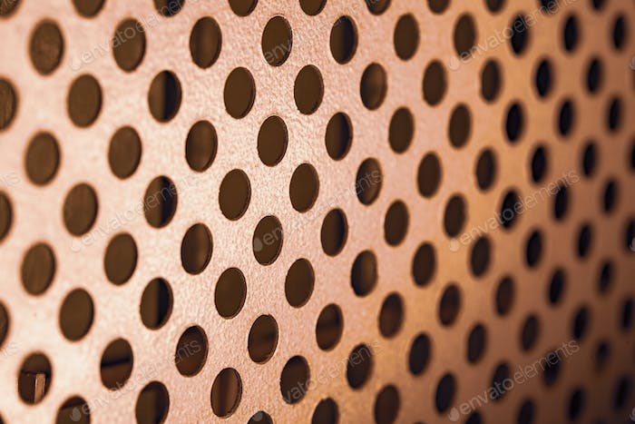 Close-up of a metal grill with round holes