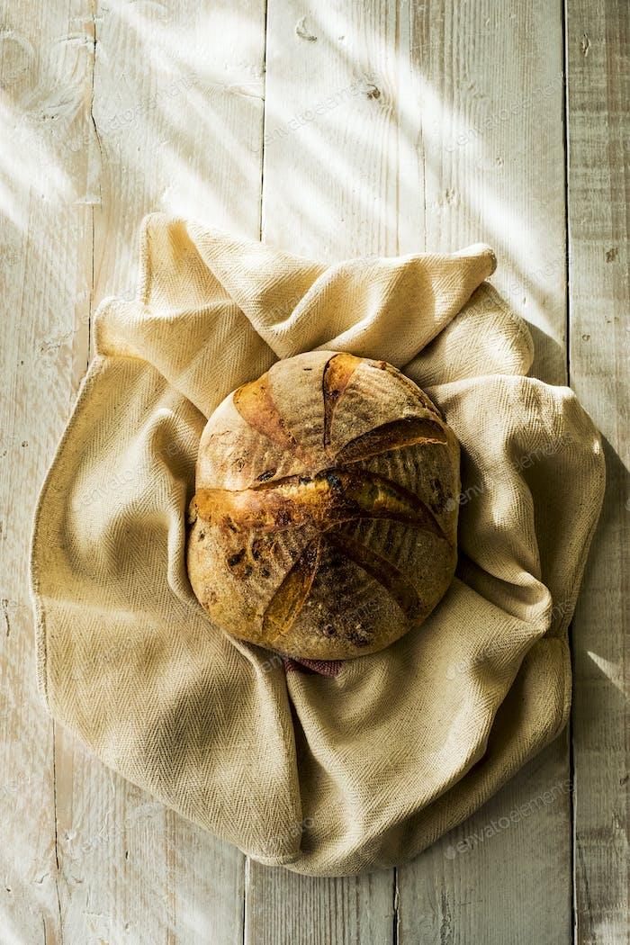 Hochwinkelnaher Nahaufnahme eines frisch gebackenen runden Brotlaib auf Geschirrtuch.
