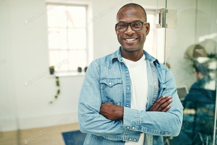 Lächelnd junge afrikanische Geschäftsmann arbeitet in einem modernen Büro