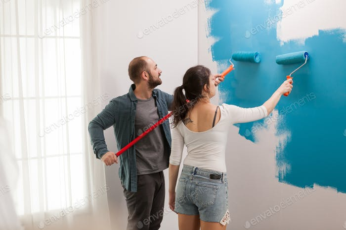 Husband helps his wife to paint