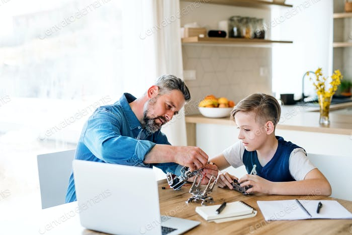 Mature father with small son sitting at table indoors, working on school project