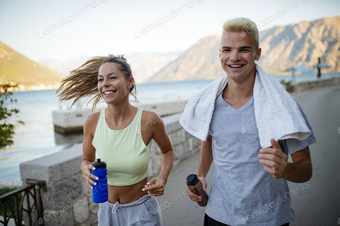 Happy fit people couple jogging and running outdoors
