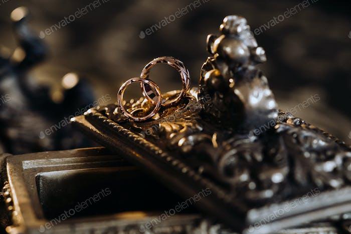 Goldene Trauringe liegen auf einer antiken Schmuckschatulle. Trauringe für Zeremonien