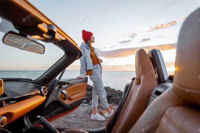Woman traveling by car on the rocky ocean coast