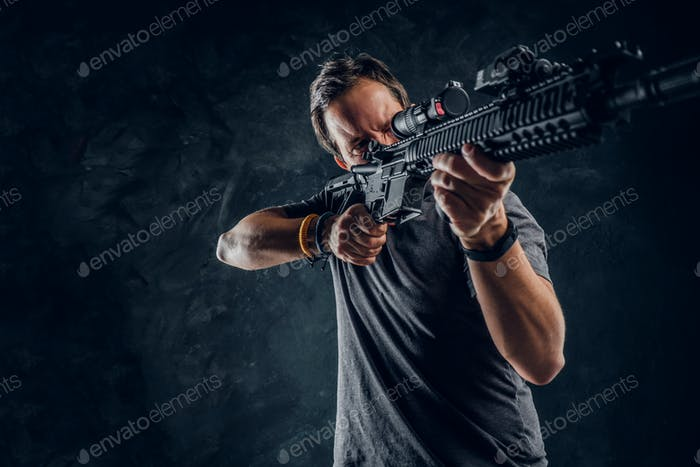 Distraught middle-aged man dressed in casual clothes holding an assault rifle