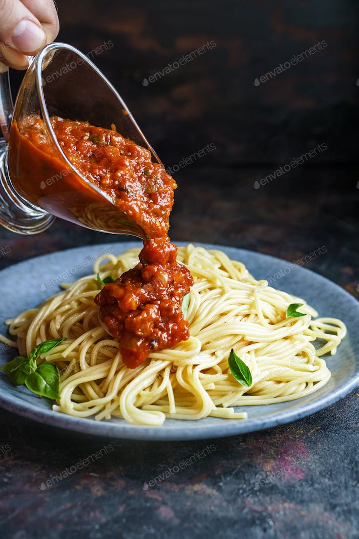 Pouring spaghetti with tomato sauce