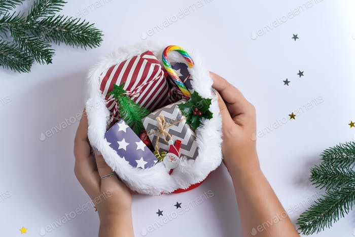 Christmas card with woman's hand and hat filled gifts