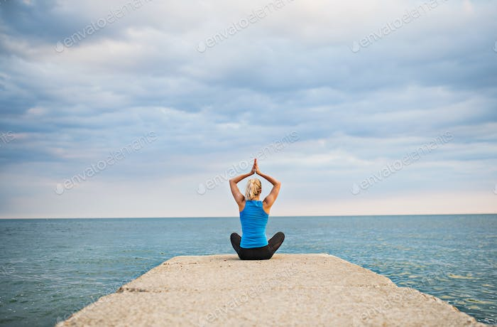 Rear view of a young sporty woman doing yoga exercise by the ocean outside.