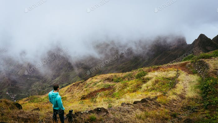 Panoramic shot of traveler taking picture of amazing steep mountain range and terrain canyon valley