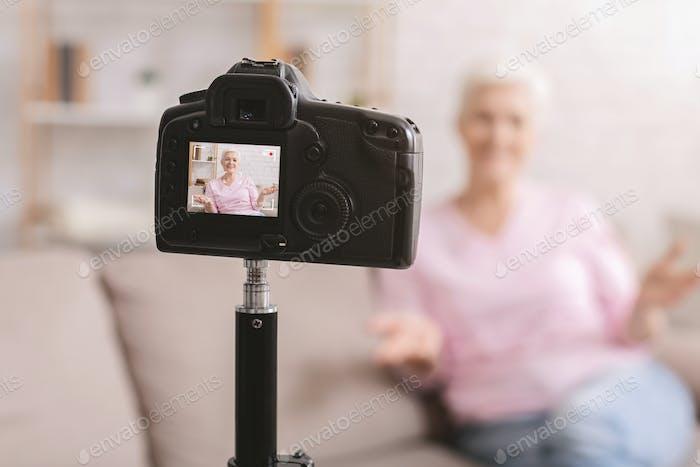 Senior woman blogger recording video vlog at home
