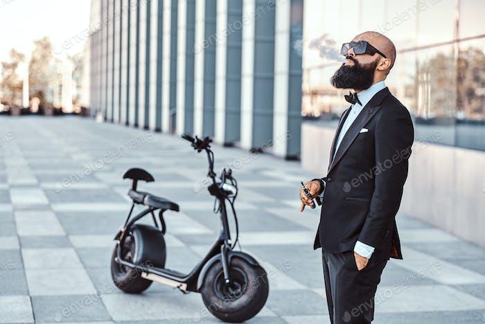 Элегантный человек курит рядом с электро велосипедом
