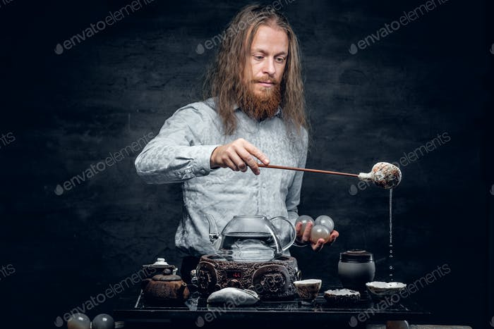 Positive bearded male pours hot tea.