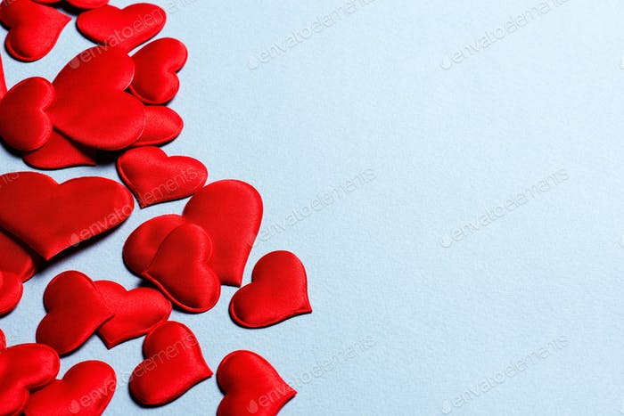 Festive Background with Red Satin Hearts on Blue