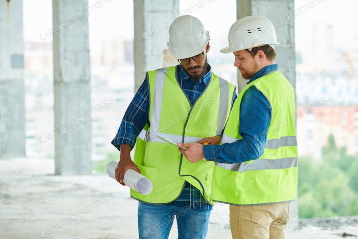 Construction engineers studying project on tablet