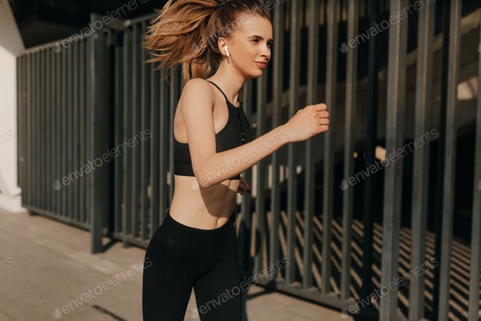 Photo of attractive woman in fashionable sportswear. Dynamic movement. Sport and healthy lifestyle.