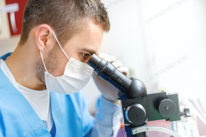 Close-up of man researcher using a microscope, examination of sa