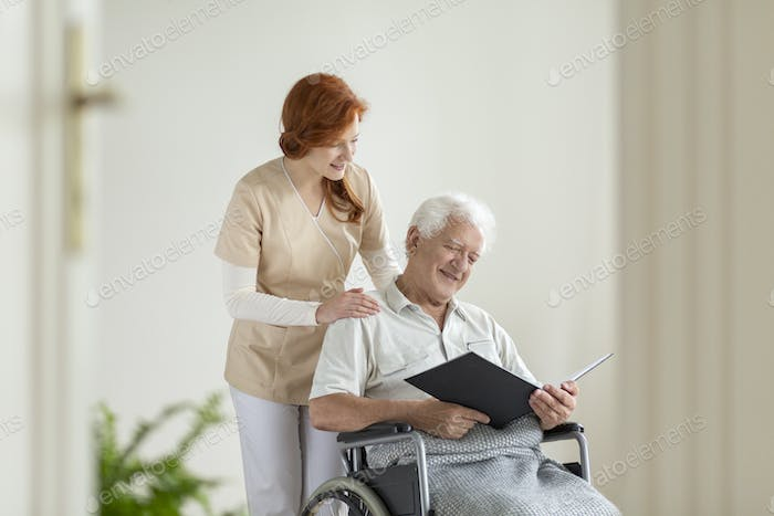 Happy elderly man in the wheelchair reading a book during visit