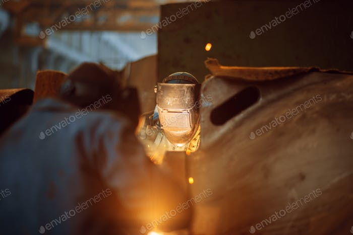 Two welder in masks works with metal, welding
