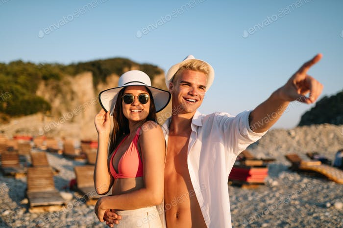 Happy couple in love walking on beach on honeymoon vacation