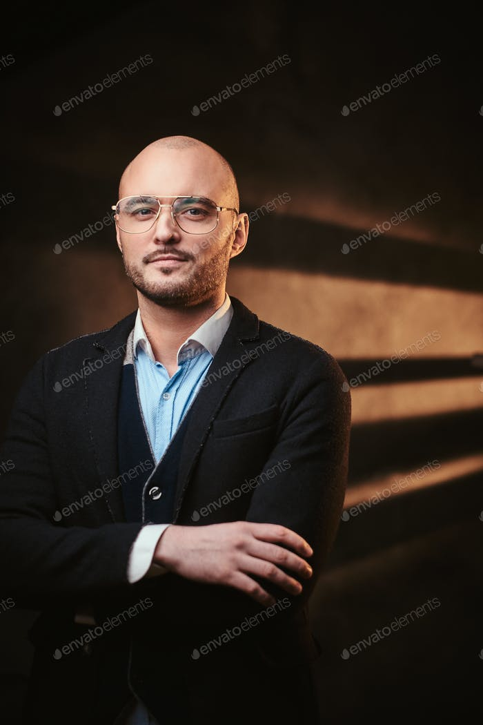 Handsome bald businessman posing in a dark studio wearing black jacket, blue shirt and glasses.