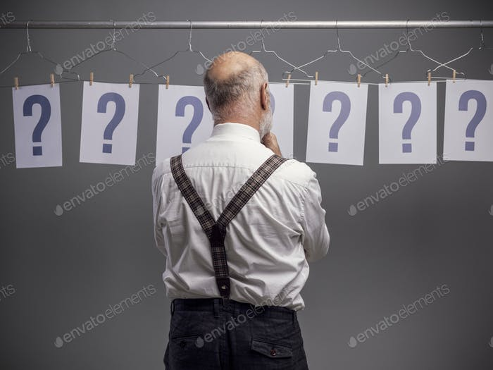 Pensive man comparing different possibilities and questions