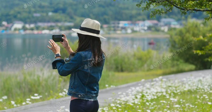 Woman travel in the landscape and take photo on cellphone