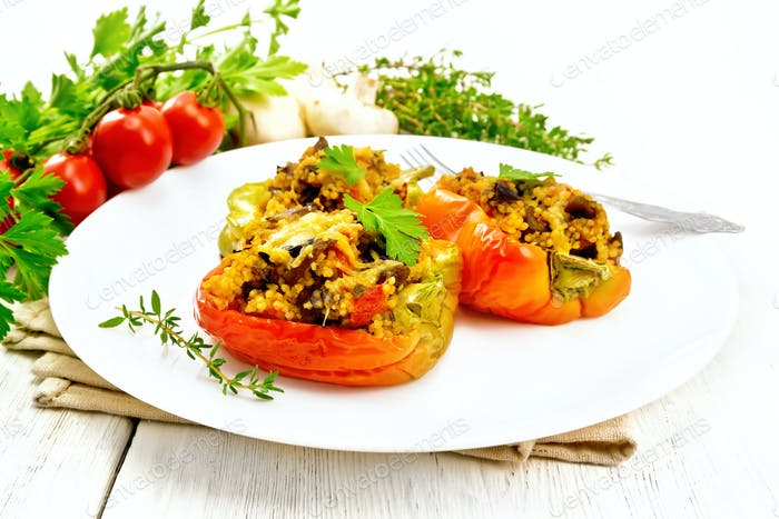 Pepper stuffed with mushrooms and couscous in plate on table
