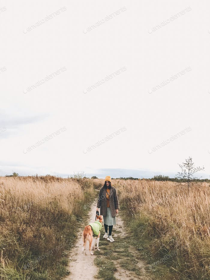 Stylish Hipster girl in yellow hat and coat walking with her golden dog
